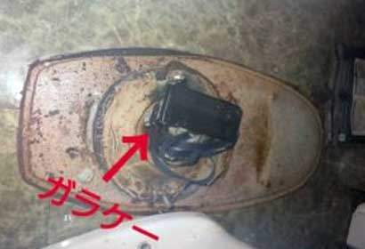 排水口につまった携帯電話(ガラケー)
